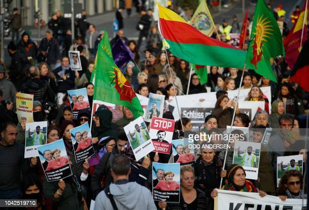 Demonstrators protesting against the policy of the Turkish President hold placards showing German Chancellor Angela Merkel and Turkish President...