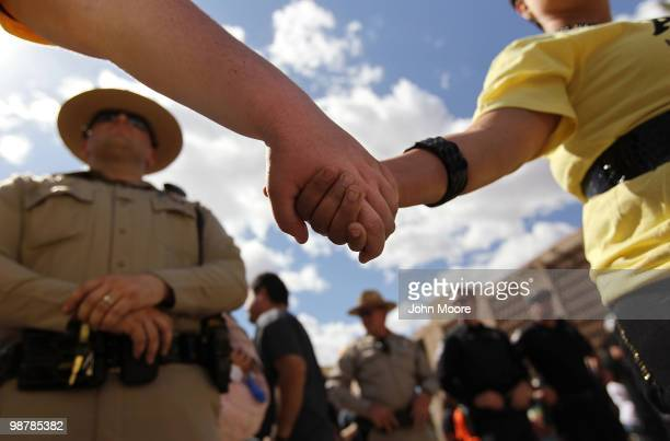 Demonstrators protesting Arizona's new immigration law clasp hands in front of a police line during a May Day rally at the state capitol building on...