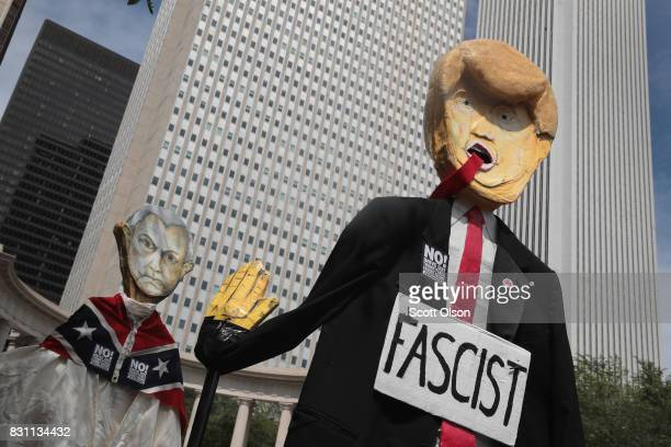 Demonstrators protesting the alt-right movement and mourning the victims of yesterdays rally in Charlottesville, Virginia carry puppets of President...
