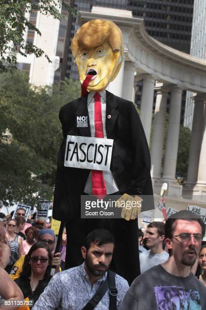 Demonstrators protesting the alt-right movement and mourning the victims of yesterdays rally in Charlottesville, Virginia carry a puppet of President...
