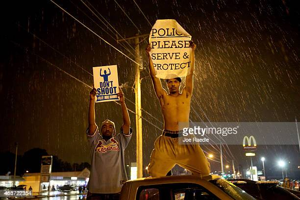 Demonstrators protesting the shooting death of Michael Brown hold signs on August 16, 2014 in Ferguson, Missouri. Violent outbreaks have taken place...