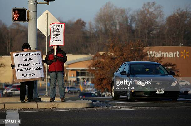 Demonstrators protesting the shooting death of Michael Brown hold signs near the entrance to a local Walmart store on Black Friday November 28 2014...