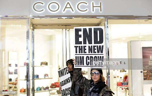 Demonstrators protesting the shooting death of Michael Brown walk past a Coach store at Saint Louis Galleria mall chanting during Black Friday...