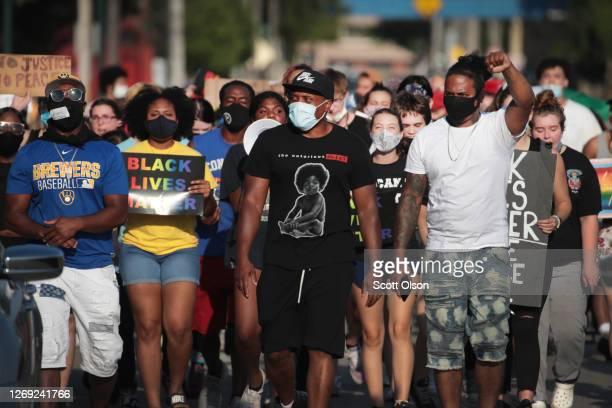 Demonstrators protesting the shooting of Jacob Blake march through a neighborhood on August 27 2020 in Kenosha Wisconsin Blake was shot seven times...