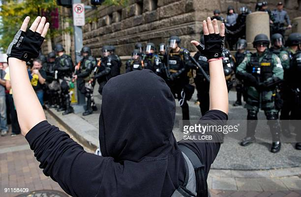 A demonstrators protests in front of police officers dressed in riot gear prior to joining thousands of marchers through downtown Pittsburgh...