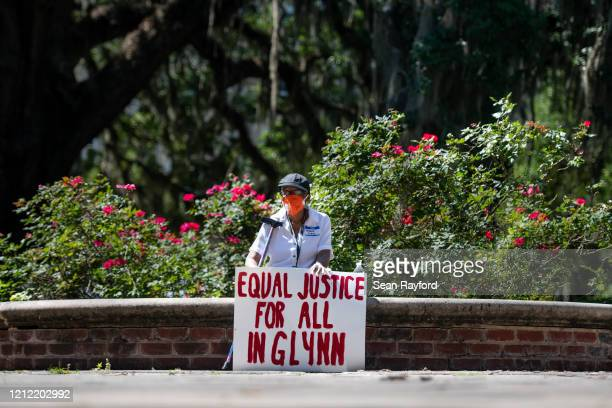 A demonstrators protests the shooting death of Ahmaud Arbery at the Glynn County Courthouse on May 8 2020 in Brunswick Georgia Gregory McMichael and...