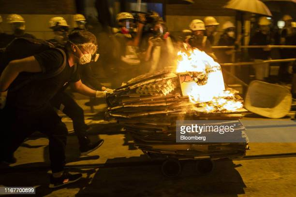 Demonstrators push a cart with cardboard boxes set on fire towards riot police during a protest in the Sheung Wan district of Hong Kong, China, on...