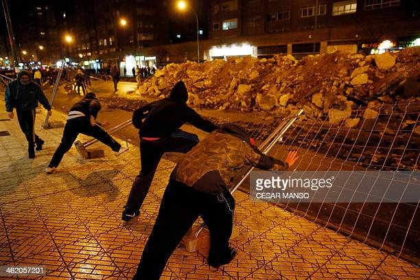 Demonstrators push down fencing in protest against imminent construction works to revamp Vitoria street the city's main thoroughfare in Burgos on...