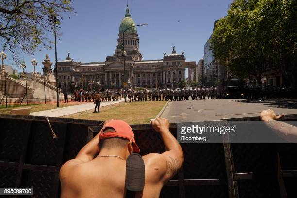 Demonstrators push on metal barriers as police officers stand guard in front of the national congress building during protests against pension...