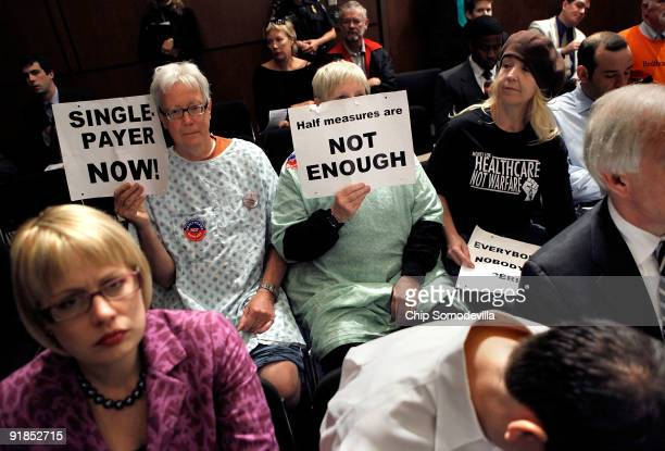 Demonstrators quietly protest during a full hearing of the Senate Finance Committee which is set to vote on health care reform legislation on Capitol...