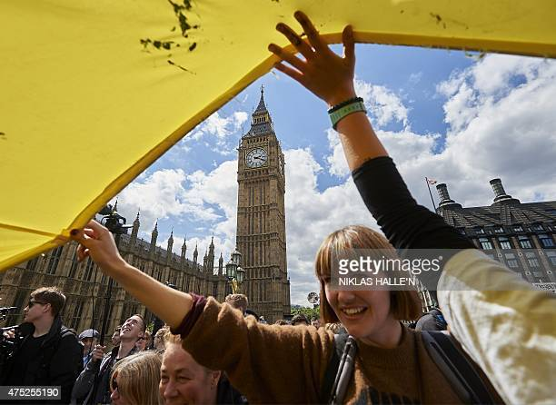 Demonstrators raise a banner in front of the Houses of Parliament as they take part in a protest against the Conservative government's austerity...