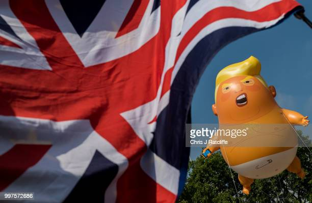 Demonstrators raise a six meter high effigy of Donald Trump being dubbed the 'Trump Baby' in Parliament Square in protest against the US President's...