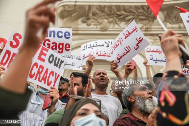 Demonstrators raise placards that read in Arabic, down with the coup against the constitution, during a demonstration held in the capital Tunis,...