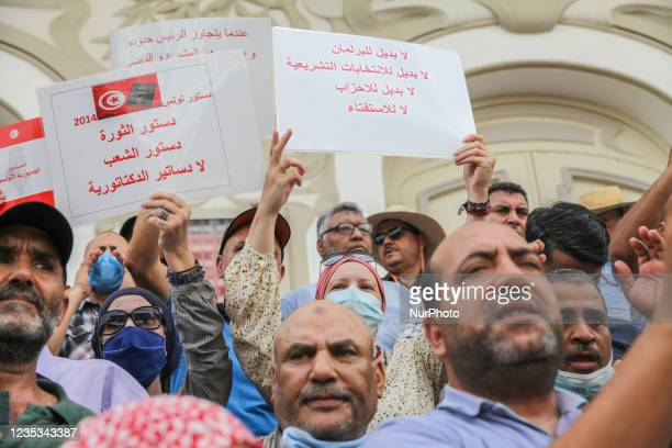 Demonstrators raise placards that read in Arabic, the constitution of the revolution, constitution of the people, no constitutions of dictatorships,...
