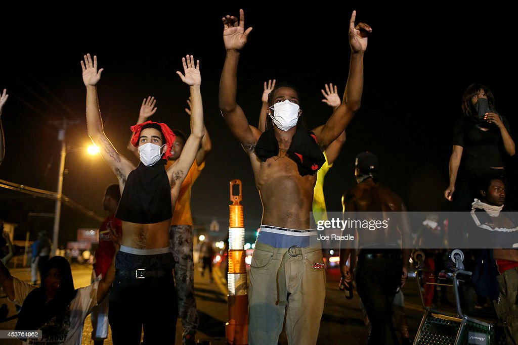 Demonstrators raise their arms and chant, 'Hands up, Don't Shoot', as police clear them from the street as they protest the shooting death of Michael Brown on August 17, 2014 in Ferguson, Missouri. Police sprayed pepper spray, shot smoke, gas and flash grenades as violent outbreaks have taken place in Ferguson since the shooting death of Michael Brown by a Ferguson police officer on August 9th.