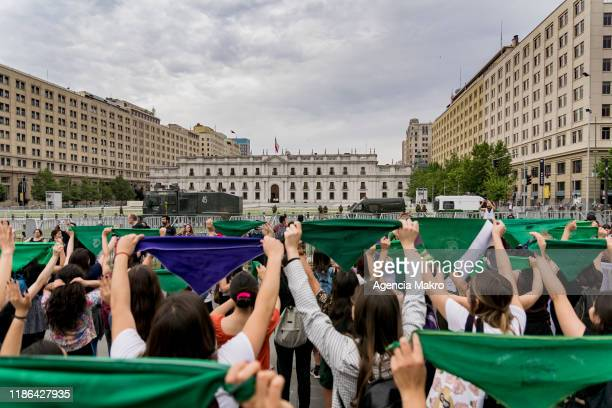 Demonstrators raise their bandanas demanding safe and legal abortion during a protest against the government of president Sebastian Piñera in front...