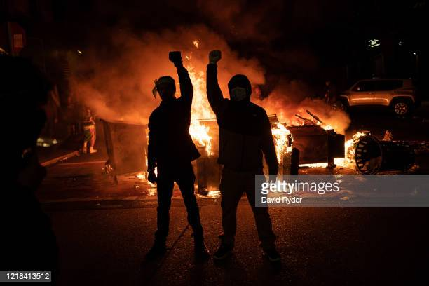 Demonstrators raise their fists as a fire burns in the street after clashes with law enforcement near the Seattle Police Departments East Precinct...
