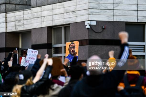 Demonstrators raise their fists as they protest outside the Hennepin County Government Center during jury selection at the trial of former...