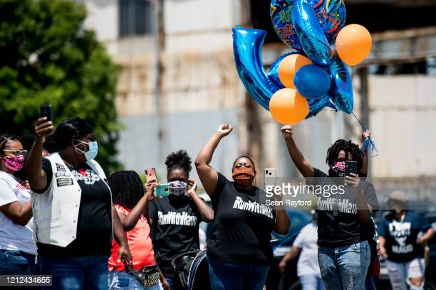 Demonstrators raise their fists at a parade of passing motorcyclists riding in honor of Ahmaud Arbery on May 9 2020 at Sidney Lanier Park in...