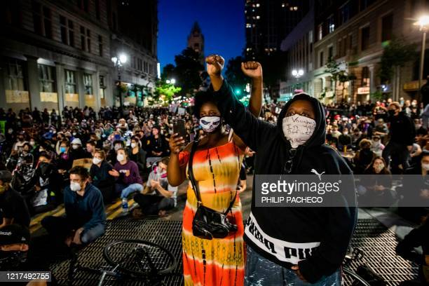 "Demonstrators raise their fists during a ""Sit Out the Curfew"" protest against the death of George Floyd who died on May 25 in Minneapolis whilst in..."