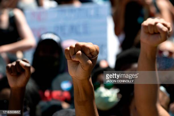 TOPSHOT Demonstrators raise their fists in a sign of solidarity on May 30 2020 in Denver Colorado while protesting the death of George Floyd an...