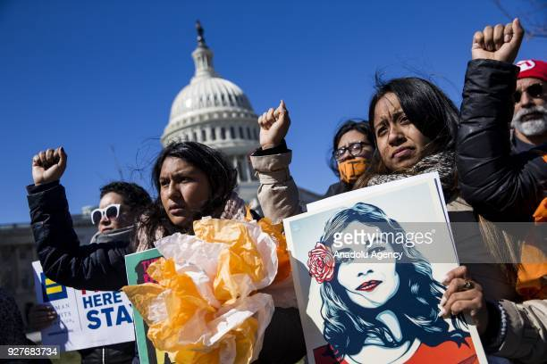 Demonstrators raise their fists in protest of President Trump's attempts to end the Deferred Action for Childhood Arrivals an executive action made...