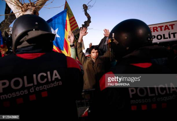 Demonstrators raise their hands as they stand in front of 'Mossos D'Esquadra' officers during a demonstration outside the Catalan parliament on...