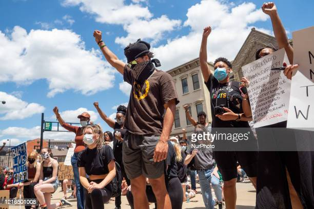 Demonstrators raise their hands during a Mass Action for Black Liberation protest and march from Washington Park to City Hall following the alleged...