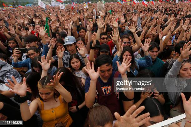 Demonstrators raise their hands for a minute of silence for the deceased in the protests during the day of cultural activities called by 'Movimiento...