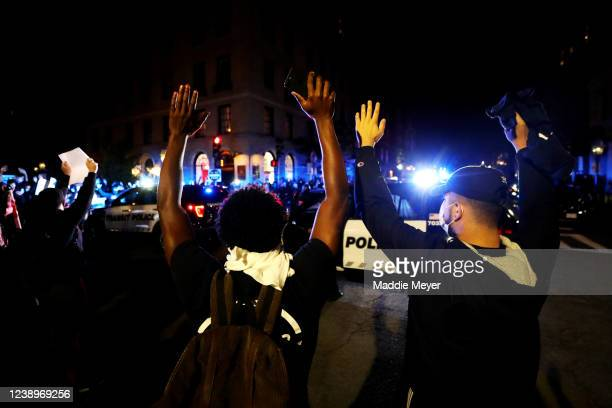 Demonstrators raise their hands in front of police cars during a protest in response to the recent death of George Floyd on May 31, 2020 in Boston,...