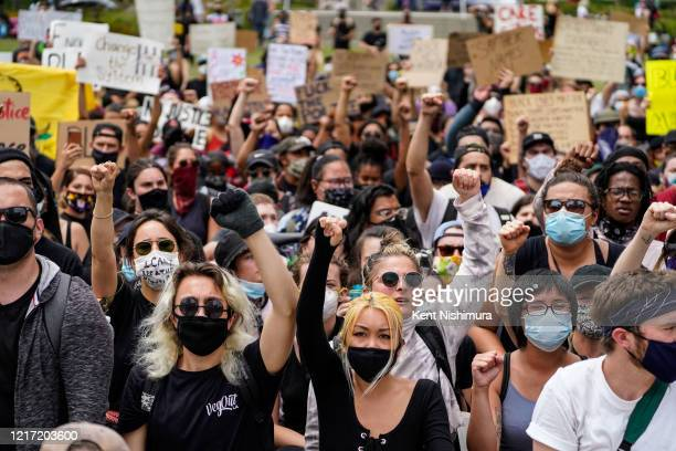 Demonstrators raise their hands into the air chanting at Grand Park fronting City Hall in downtown Los Angeles on Tuesday June 2 2020 in Los Angeles...