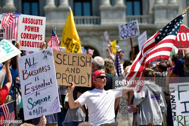 Demonstrators rally outside the Pennsylvania Capitol Building to protest the continued closure of businesses due to the coronavirus pandemic on May...
