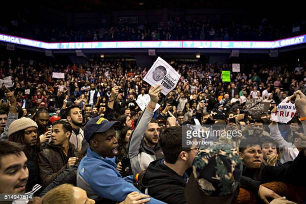 Demonstrators react after the cancellation of a campaign event with Donald Trump president and chief executive of Trump Organization Inc and 2016...