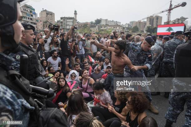 Demonstrators react as police try to forcibly remove anti-government protesters blocking a major highway in central Beirut on October 26 2019 in...