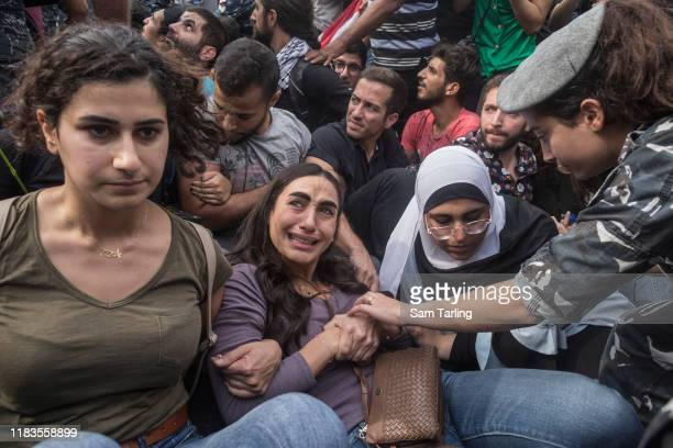 Demonstrators react as police try to forcibly remove anti-government protesters blocking a major highway in central Beirut on October 26, 2019 in...