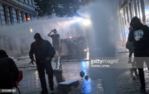 Demonstrators react in front of the police water cannon during a demonstration against the G20 Summit on July 7 2017 in Hamburg Germany Leaders of...