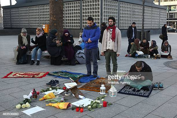 Demonstrators read holy Quran and perform prayer as they gather at Breitscheidplatz square to protest against the Chapel Hill shooting in Berlin...