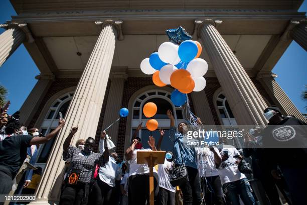 Demonstrators release balloons during a protest of the shooting death of Ahmaud Arbery at the Glynn County Courthouse on May 8 2020 in Brunswick...