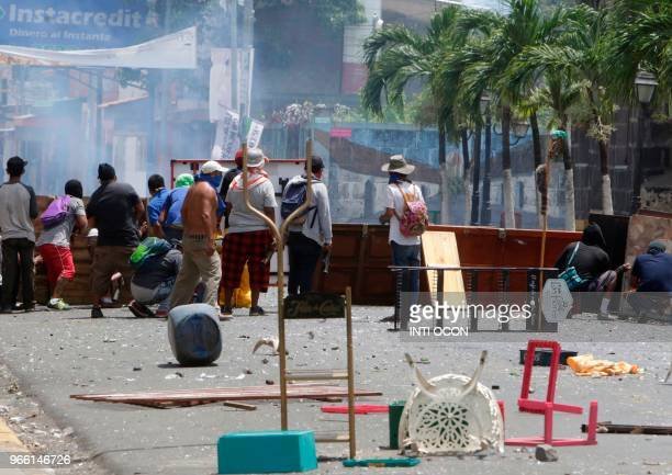 Demonstrators remain behind an improvised barricade during clashes with riot police within protests in Monimbo neighborhood in Masaya some 40km from...