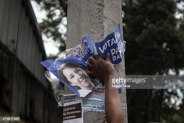 Demonstrators remove election posters after a rally to ask Mexican authorities to continue the search for the 43 kidnapped students by local police...
