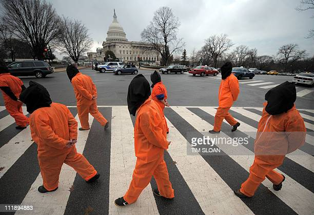 Demonstrators representing prisoners at the US Guantanamo Bay Naval Base walk during a rally against torture sponsored by Witness Against Torture...