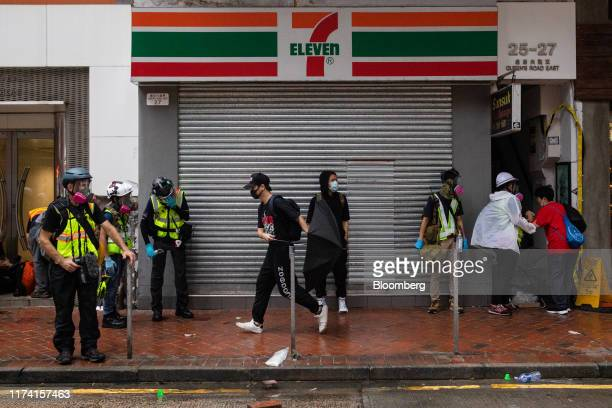 Demonstrators rest outside a shuttered 7Eleven store operated by Dairy Farm International Holdings Ltd during a protest in the Wan Chai district of...