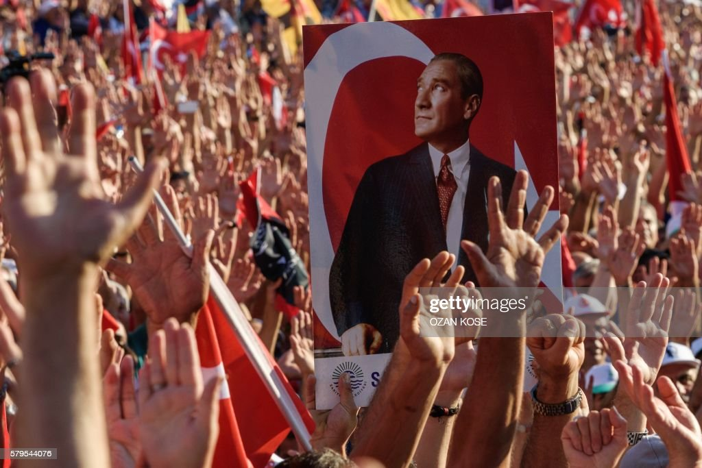 TOPSHOT - Demonstrators rise their hands and hold a potrait picture of Mustafa Kemal Ataturk, founder of modern Turkey, as they gather at Taksim Square in Istanbul on July 24, 2016. - Many thousands of flag-waving Turks massed on July 24, 2016, for the first cross-party rally to condemn the coup attempt against President Recep Tayyip Erdogan, amid an ongoing purge of suspected state enemies. Several banners also protested the post-coup state of emergency, with one proclaiming 'No to the coup, no to dictatorship' and another saying 'Turkey is secular and will remain so'. The mass event was called by the biggest opposition group, the secular and centre-left Republican People's Party (CHP), many of whose members carried pictures of modern Turkey's founding father Mustafa Kemal Ataturk.