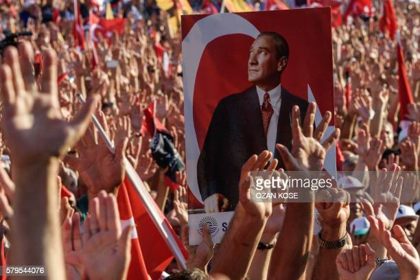 Demonstrators rise their hands and hold a potrait picture of Mustafa Kemal Ataturk, founder of modern Turkey, as they gather at Taksim Square in...