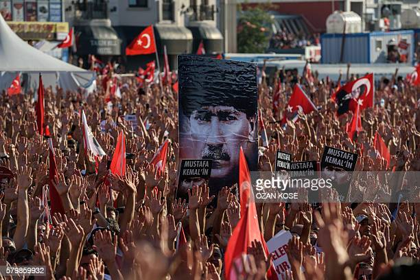 Demonstrators rise their hands and hold a potrait picture of Mustafa Kemal Ataturk founder of modern Turkey as they gather at Taksim Square in...
