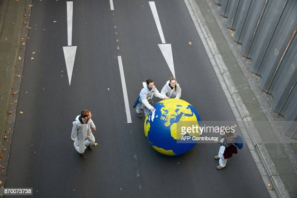 Demonstrators roll a giant globe through a street as they take part in a socalled Climate March against fossilbased energy like coal on November 4...