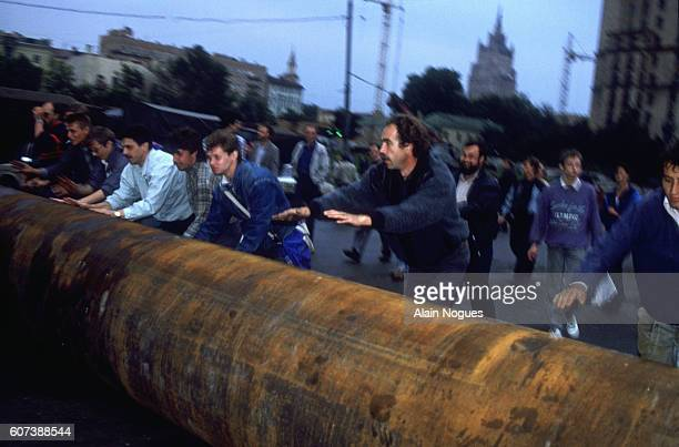 Demonstrators roll a large metal pipe through the streets of Moscow to help form a barricade outside the Russian White House during a 1991 coup...