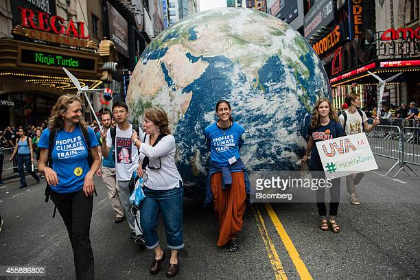 Demonstrators roll a model of the planet Earth down the street during the People's Climate March in New York US on Sunday Sept 21 2014 The United...