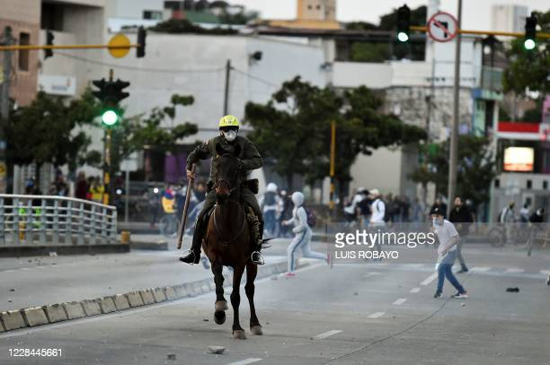 TOPSHOT Demonstrators run as a mounted police officer chases them during clashes with riot police which erupted during a protest against the death of...