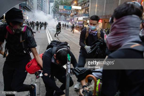 Demonstrators run as riot police charge during a protest in the Wan Chai district of Hong Kong China on Sunday Oct 6 2019 Violence escalated in Hong...